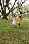 two girls holding hands, skipping in woods