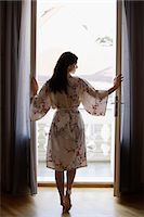 fragile - young woman standing at open doorway Stock Photo - Premium Royalty-Freenull, Code: 6106-06309741