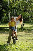 Mother pushing her son in a tree swing. Stock Photo - Premium Royalty-Freenull, Code: 6106-06309895