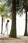 Woman walking under coconut trees on beach. Stock Photo - Premium Royalty-Free, Artist: CulturaRM, Code: 6106-06310021