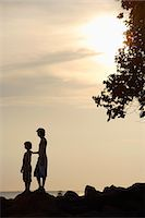 Silhouette of two young boys standing on rocks on shore Stock Photo - Premium Royalty-Freenull, Code: 6106-06310633