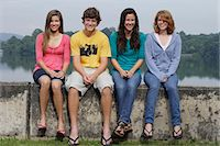 Group of teens sitting on wall next to lake Stock Photo - Premium Royalty-Freenull, Code: 6106-06310670