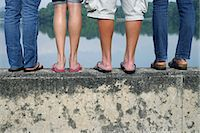 legs of teens standing on wall near lake Stock Photo - Premium Royalty-Freenull, Code: 6106-06310676