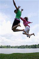Teen girls jumping by lake Stock Photo - Premium Royalty-Freenull, Code: 6106-06310683