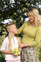 family apple orchard - mother and daughter under apple tree Stock Photo - Premium Royalty-Freenull, Code: 6106-06311299