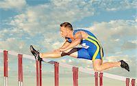 Male hurdler clearing hurdle Stock Photo - Premium Royalty-Freenull, Code: 614-06311625