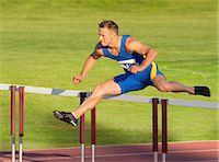 Male hurdler clearing hurdle Stock Photo - Premium Royalty-Freenull, Code: 614-06311626