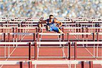 Male hurdler clearing hurdles Stock Photo - Premium Royalty-Freenull, Code: 614-06311629