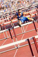 Male hurdler clearing hurdles Stock Photo - Premium Royalty-Freenull, Code: 614-06311630