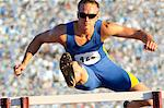 Male hurdler cleaning hurdle Stock Photo - Premium Royalty-Free, Artist: Cultura RM, Code: 614-06311633