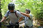 Mountain biker fixing friend's backpack Stock Photo - Premium Royalty-Free, Artist: AWL Images, Code: 614-06311968