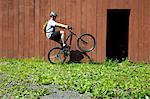 Mountain biker riding on one wheel outside barn Stock Photo - Premium Royalty-Free, Artist: AWL Images, Code: 614-06311980