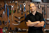 Man in front of wall of tools in workshop Stock Photo - Premium Royalty-Freenull, Code: 614-06311987