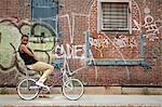 Portrait of a young woman on bicycle by wall covered in graffiti Stock Photo - Premium Royalty-Free, Artist: Uwe Umstätter, Code: 614-06311992