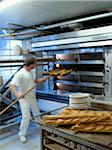 Baguettes coming out of the oven in the bakery