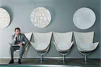 Mature businessman sitting at end of row of chairs in waiting room Stock Photo - Premium Royalty-Freenull, Code: 632-06317346