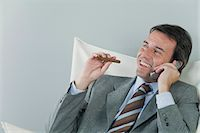 Mature businessman using cell phone and smoking cigar Stock Photo - Premium Royalty-Freenull, Code: 632-06317516