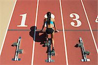 Female athlete in starting position on running track, rear view Stock Photo - Premium Royalty-Freenull, Code: 632-06317636