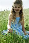 Girl sitting on grass picking flowers Stock Photo - Premium Royalty-Freenull, Code: 632-06317933