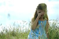 sad girls - Girl crying in field, hand rubbing eyes Stock Photo - Premium Royalty-Freenull, Code: 632-06318040
