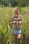 young woman standing in field Stock Photo - Premium Royalty-Free, Artist: Aurora Photos            , Code: 618-06318522
