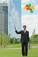 release - Businessman releasing bunch of balloons into air, looking disappointed Stock Photo - Premium Royalty-Freenull, Code: 633-06322425