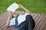Mid-adult man lying outdoors reading book Stock Photo - Premium Royalty-Free, Artist: Ty Milford, Code: 633-06322536