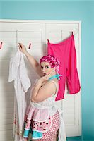 Portrait of a shocked plus-size woman drying clothes Stock Photo - Premium Royalty-Freenull, Code: 693-06323961