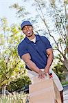 Happy young African American male pushing handtruck Stock Photo - Premium Royalty-Free, Artist: Blend Images, Code: 693-06323987