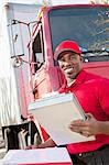 Portrait of a happy African American man holding clipboard with delivery truck in background Stock Photo - Premium Royalty-Freenull, Code: 693-06323989