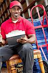 Portrait of a African American delivery man sitting on chair with clipboard Stock Photo - Premium Royalty-Freenull, Code: 693-06323995