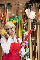 Senior female employee holding gardening tool while using mobile phone Stock Photo - Premium Royalty-Freenull, Code: 693-06324029