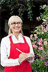 Happy senior florist making notes while looking away Stock Photo - Premium Royalty-Free, Artist: Blend Images, Code: 693-06324031