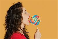 Side view of a young woman licking lollipop over colored background Stock Photo - Premium Royalty-Freenull, Code: 693-06324106
