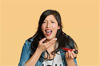 spicy - Portrait of a young woman eating red hot chili pepper over colored background Stock Photo - Premium Royalty-Freenull, Code: 693-06324124