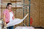 Young female contractor looking at building plans with scaffold in background Stock Photo - Premium Royalty-Free, Artist: Blend Images, Code: 693-06324427