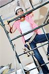 Front view of female worker climbing on scaffold Stock Photo - Premium Royalty-Free, Artist: Blend Images, Code: 693-06324431