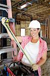 Portrait of happy female contractor with measuring tape at construction site Stock Photo - Premium Royalty-Free, Artist: Glowimages, Code: 693-06324437