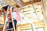 Low angle view of female worker working on incomplete ceiling Stock Photo - Premium Royalty-Free, Artist: CulturaRM, Code: 693-06324439