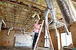 Young woman climbing up the ladder while looking at ceiling Stock Photo - Premium Royalty-Free, Artist: Uwe Umstätter, Code: 693-06324443