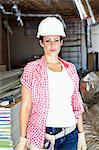 Portrait of beautiful young woman architect wearing hardhat at construction site Stock Photo - Premium Royalty-Free, Artist: Glowimages, Code: 693-06324448