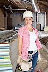 Portrait of a happy young woman architect wearing hardhat at construction site Stock Photo - Premium Royalty-Free, Artist: Blend Images, Code: 693-06324449