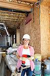 Portrait of a happy young woman with drill at construction site Stock Photo - Premium Royalty-Freenull, Code: 693-06324451