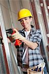 Portrait of a happy mid adult woman worker drilling at construction site Stock Photo - Premium Royalty-Free, Artist: Blend Images, Code: 693-06324463