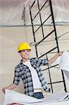 Happy mid adult worker holding building plans while looking away Stock Photo - Premium Royalty-Free, Artist: Blend Images, Code: 693-06324475