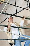 Front view of mature man climbing scaffold Stock Photo - Premium Royalty-Free, Artist: Blend Images, Code: 693-06324487