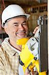 Portrait of a smiling male construction worker cutting wood with a circular saw Stock Photo - Premium Royalty-Free, Artist: Uwe Umstätter, Code: 693-06324508