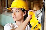 Female construction worker cutting wood with a power saw while looking away Stock Photo - Premium Royalty-Free, Artist: Blend Images, Code: 693-06324509