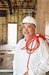Portrait of a construction worker with a red electric wire Stock Photo - Premium Royalty-Free, Artist: Blend Images, Code: 693-06324515