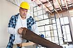 Serious male construction worker cutting wood with handsaw Stock Photo - Premium Royalty-Free, Artist: Blend Images, Code: 693-06324517